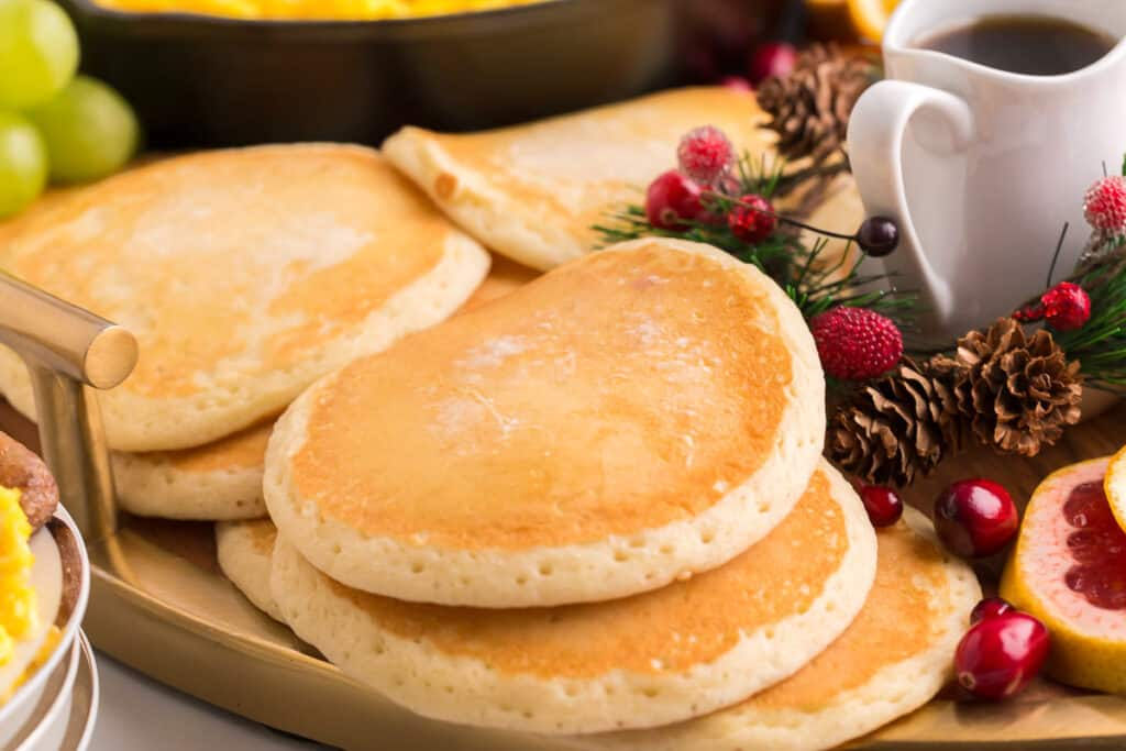 Cooked pancakes on a large platter with other breakfast items.