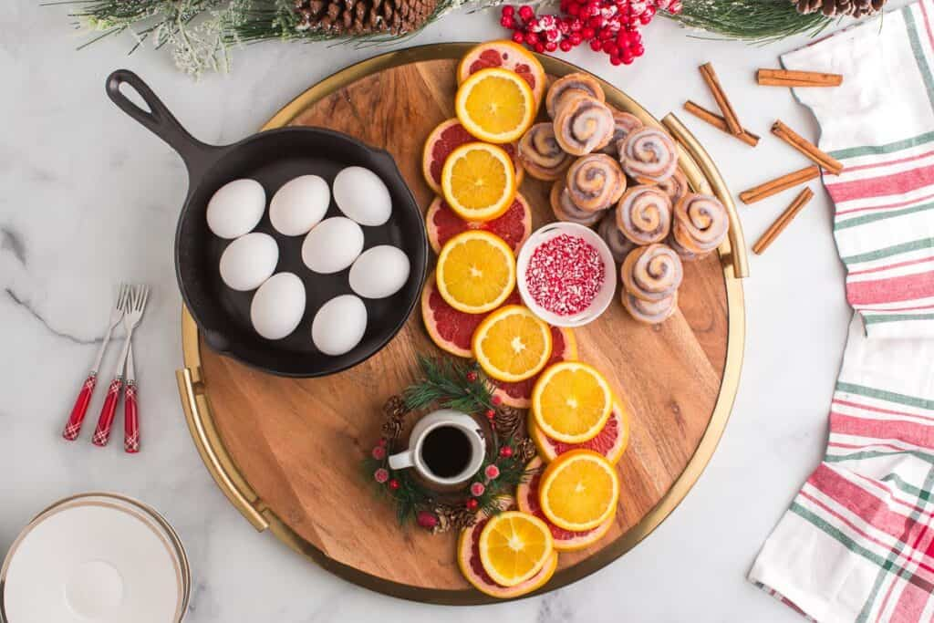 Fruit, cinnamon rolls, and small bowls arranged on a large wooden board.