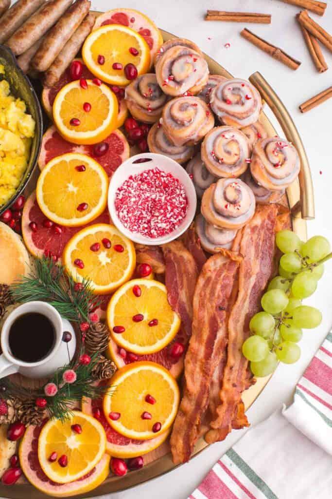 Cinnamon rolls, fruit, bacon, sausage, on a large board.
