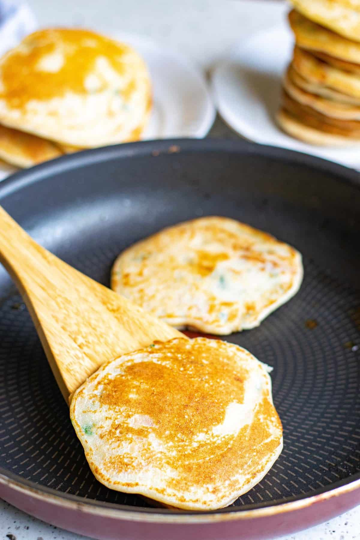 Cooked pancakes on a black frying pan.