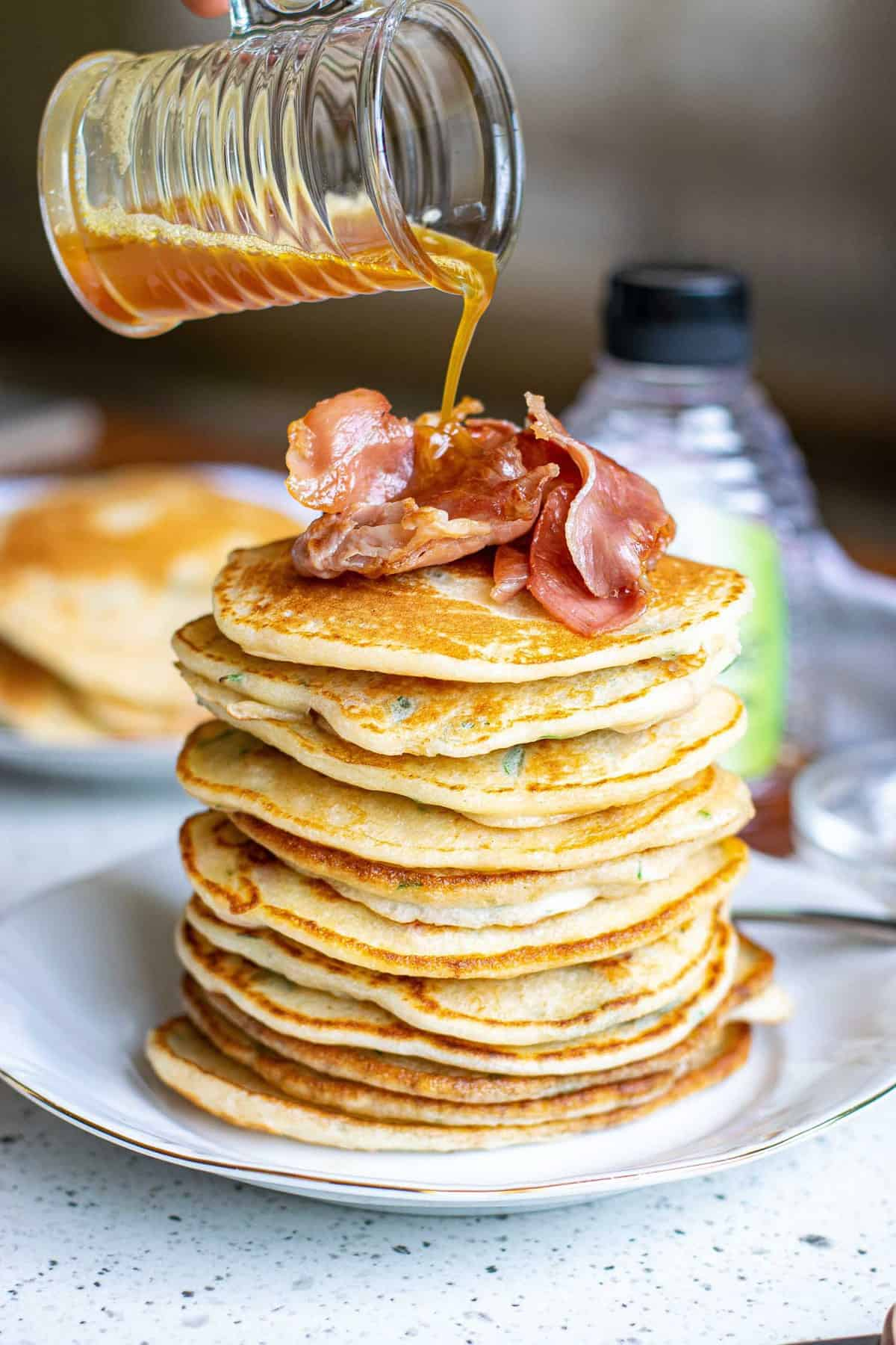 Brown butter being poured on a tall stack of pancakes.