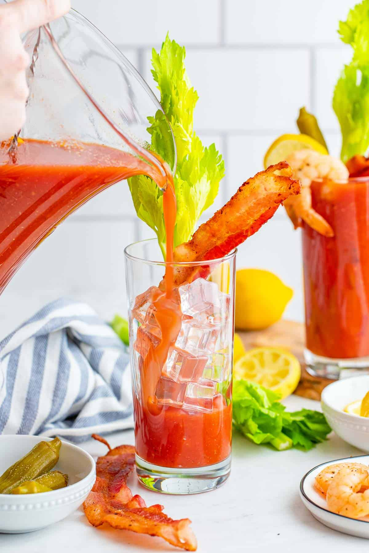 Tomato juice based bloody mary being poured over ice.