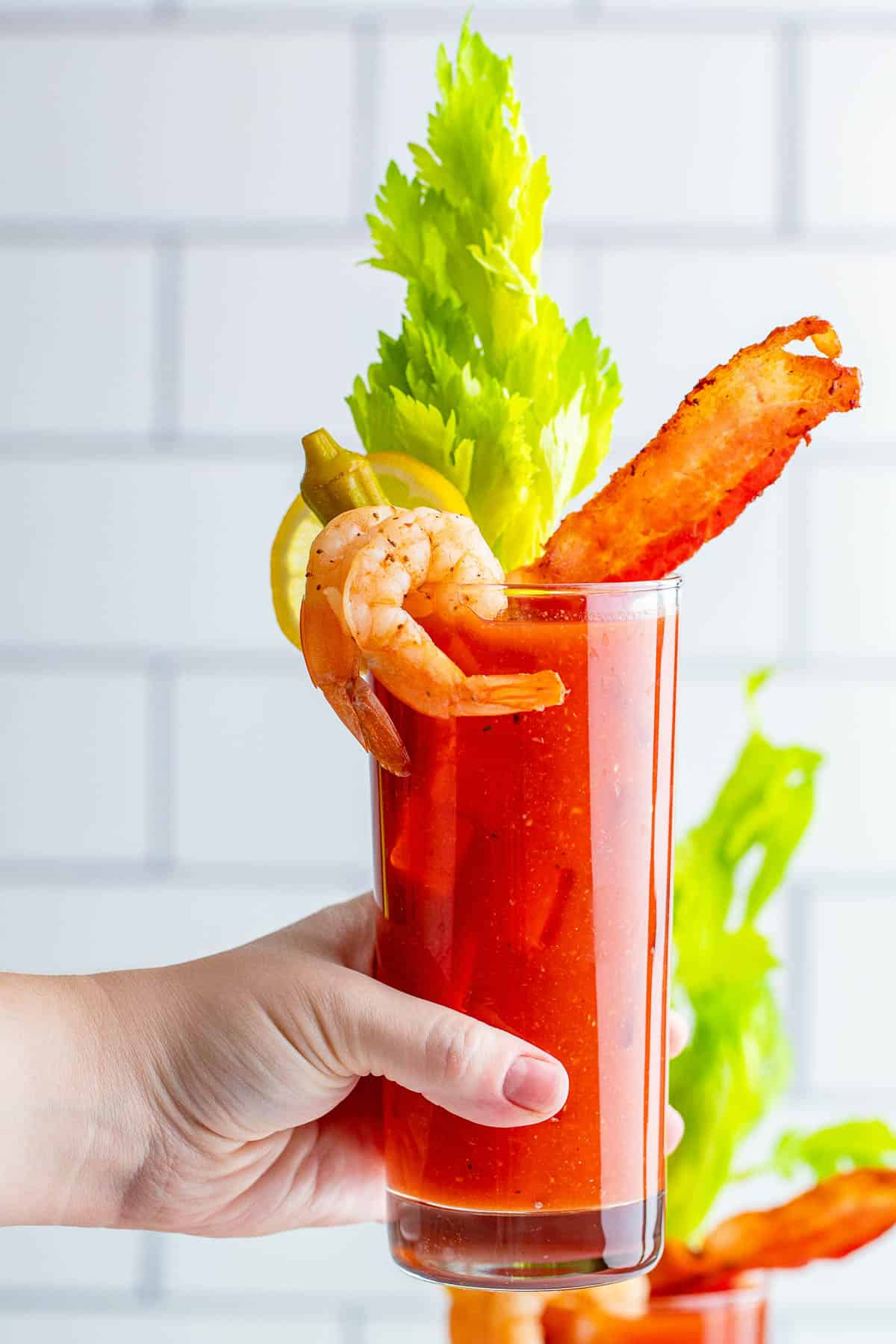 Bloody mary with shrimp, bacon, and celery in a female's hand.
