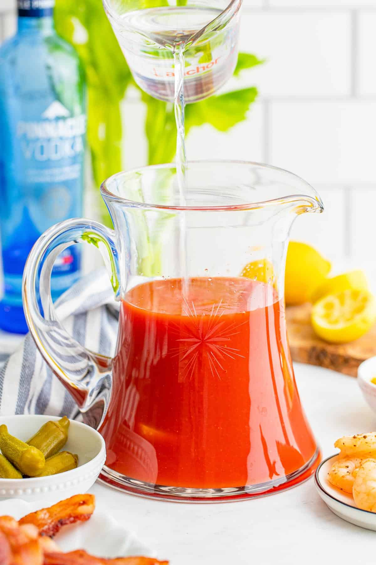Vodka being poured into a pitcher of tomato juice.