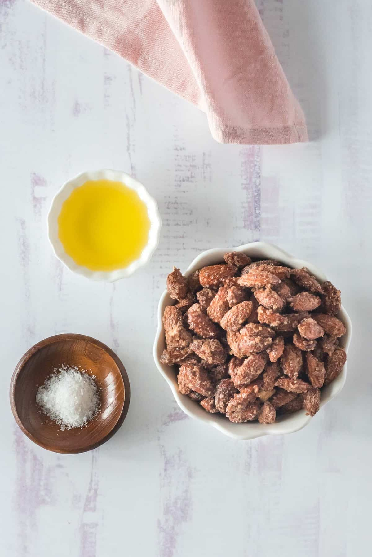 Overhead view of ingredients in bowls: almonds, salt, and oil.