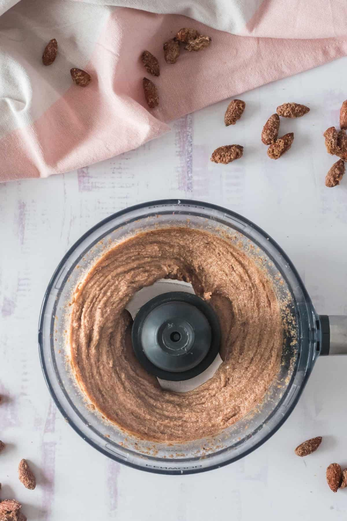 Partially blended almond butter in a food processor.