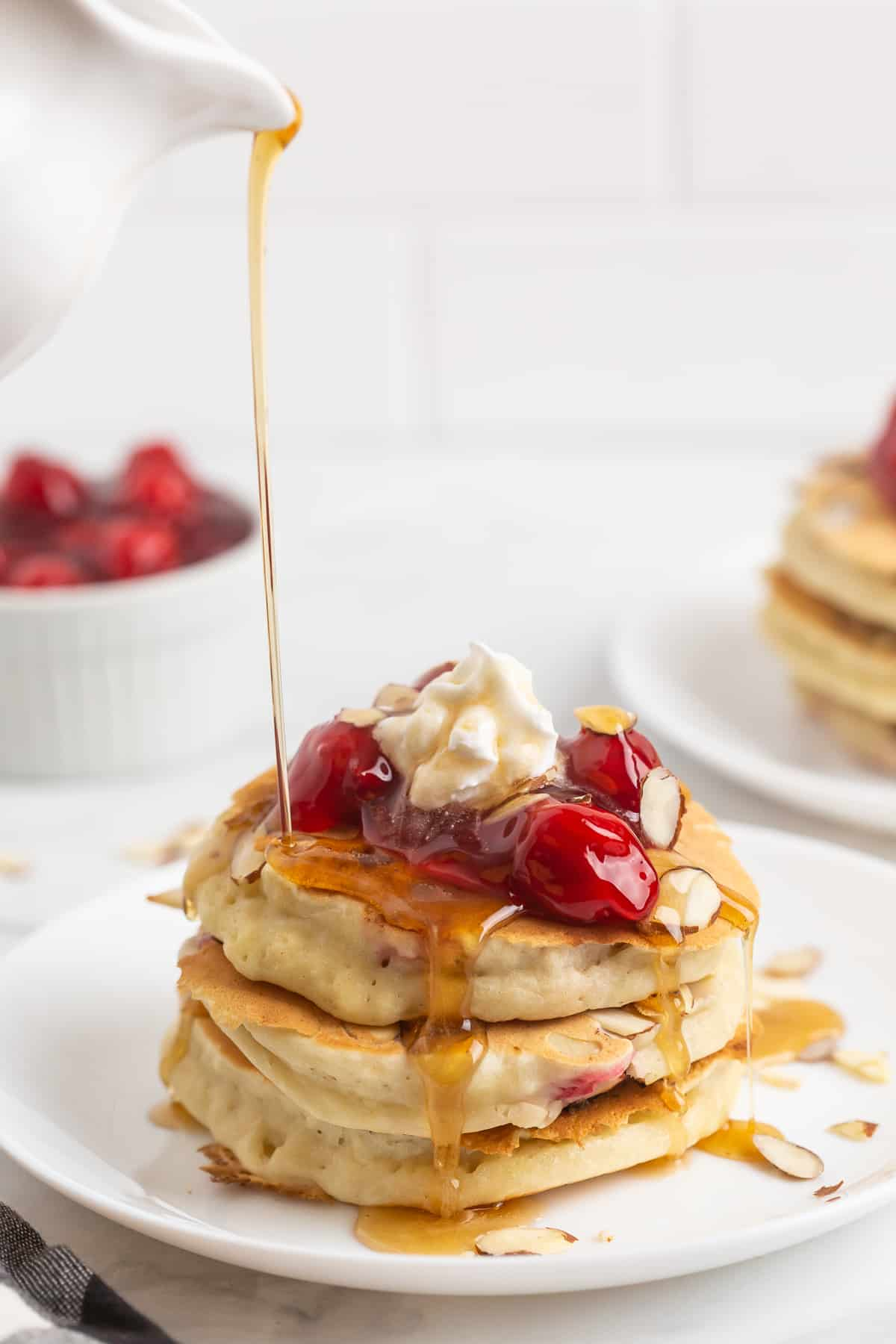 Cherries and whipped crema on top of a stack of pancakes, being drizzled with syrup.