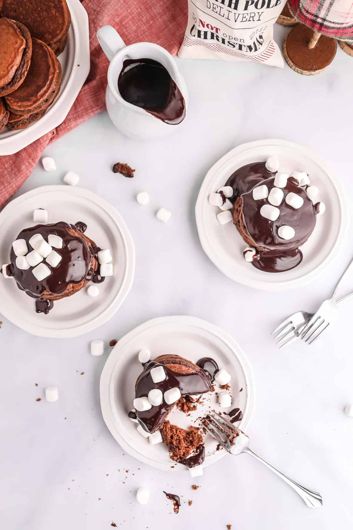 Three plates of pancakes with chocolate sauce and mini marshmallows on top.