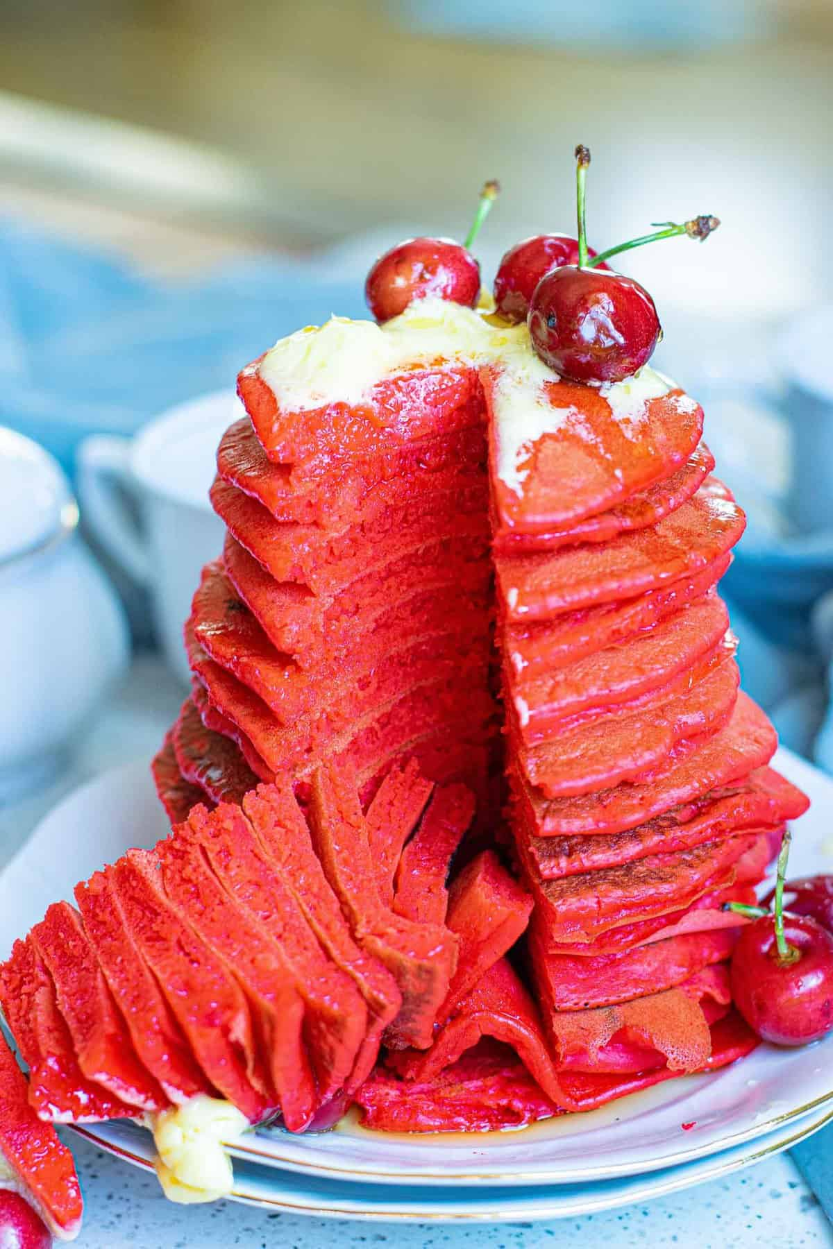 Large stack of red velvet pancakes topped with cherries.