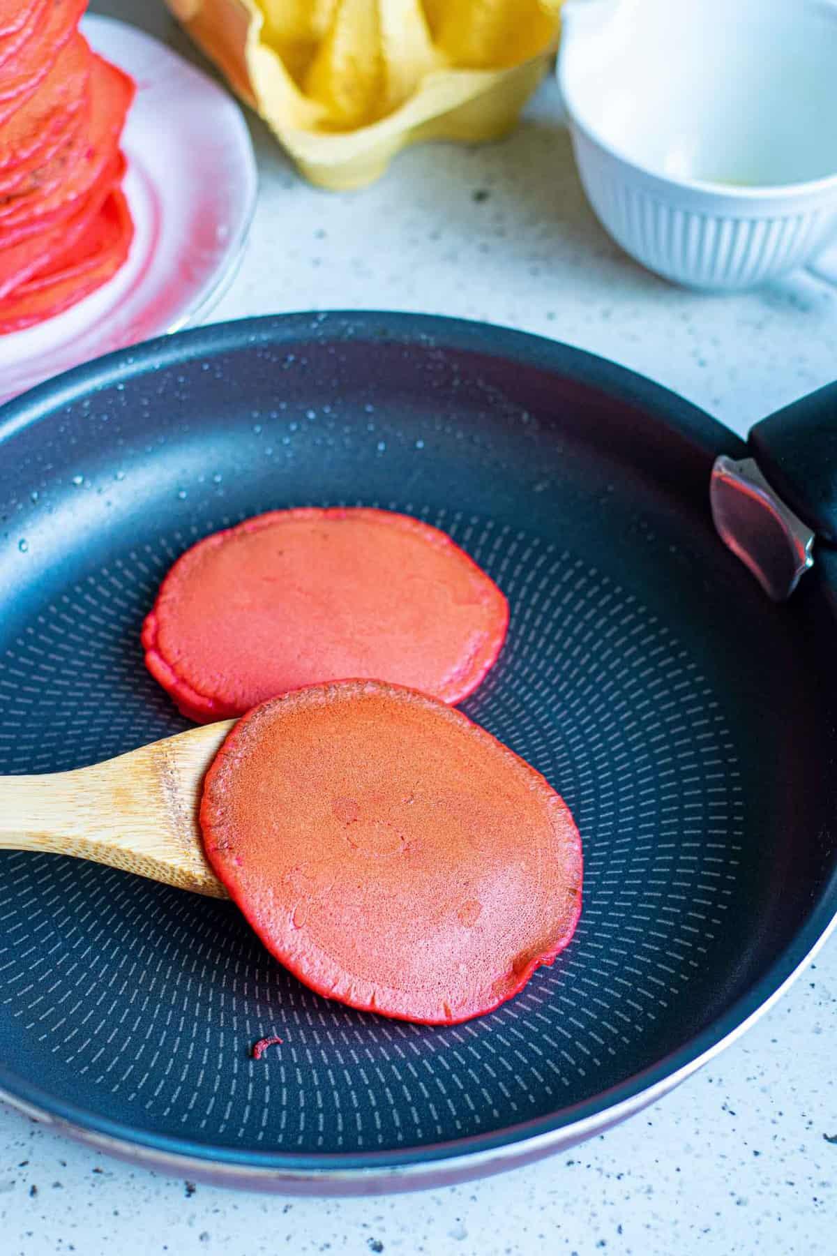 Red pancake being flipped.