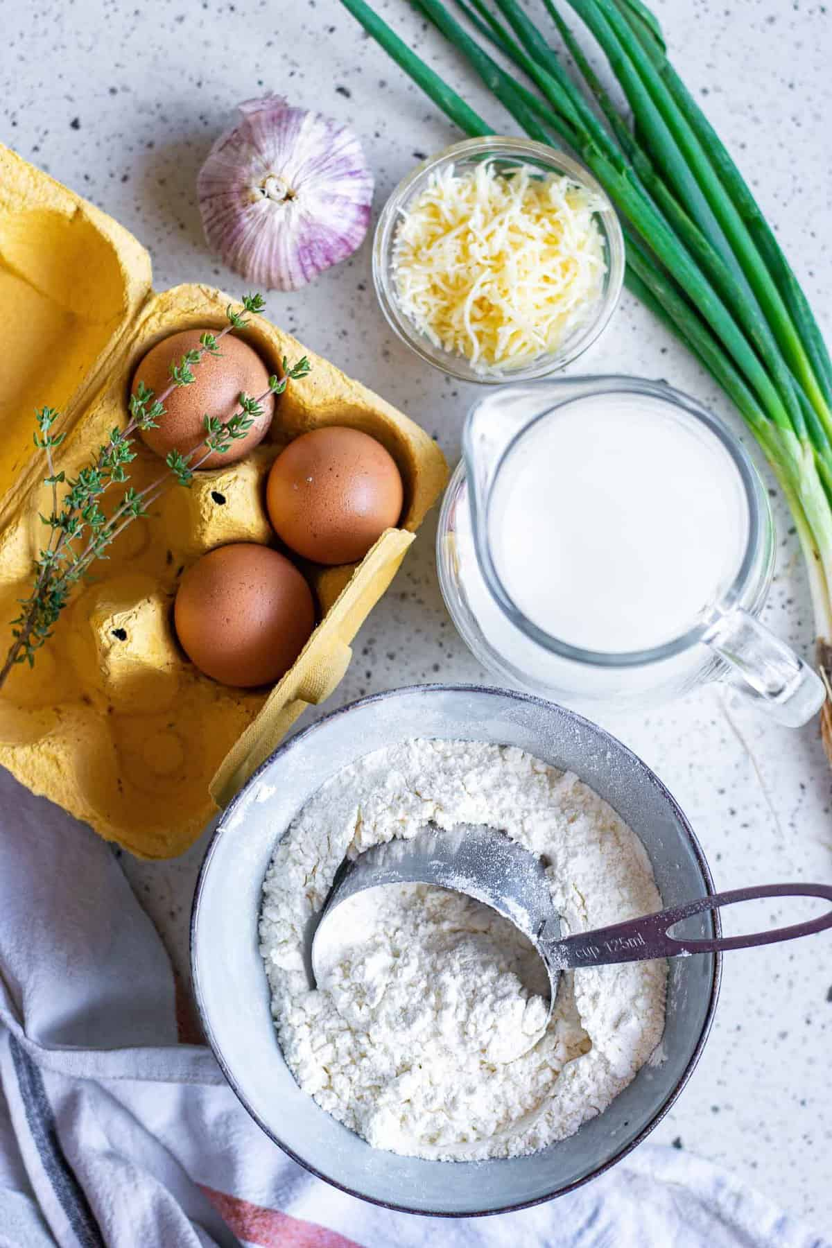 Overhead view of ingredients: flour, eggs, thyme, parmesan, green onions, garlic.