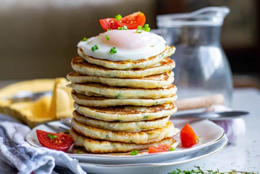 Stack of pancakes topped with an egg and fresh tomatoes.