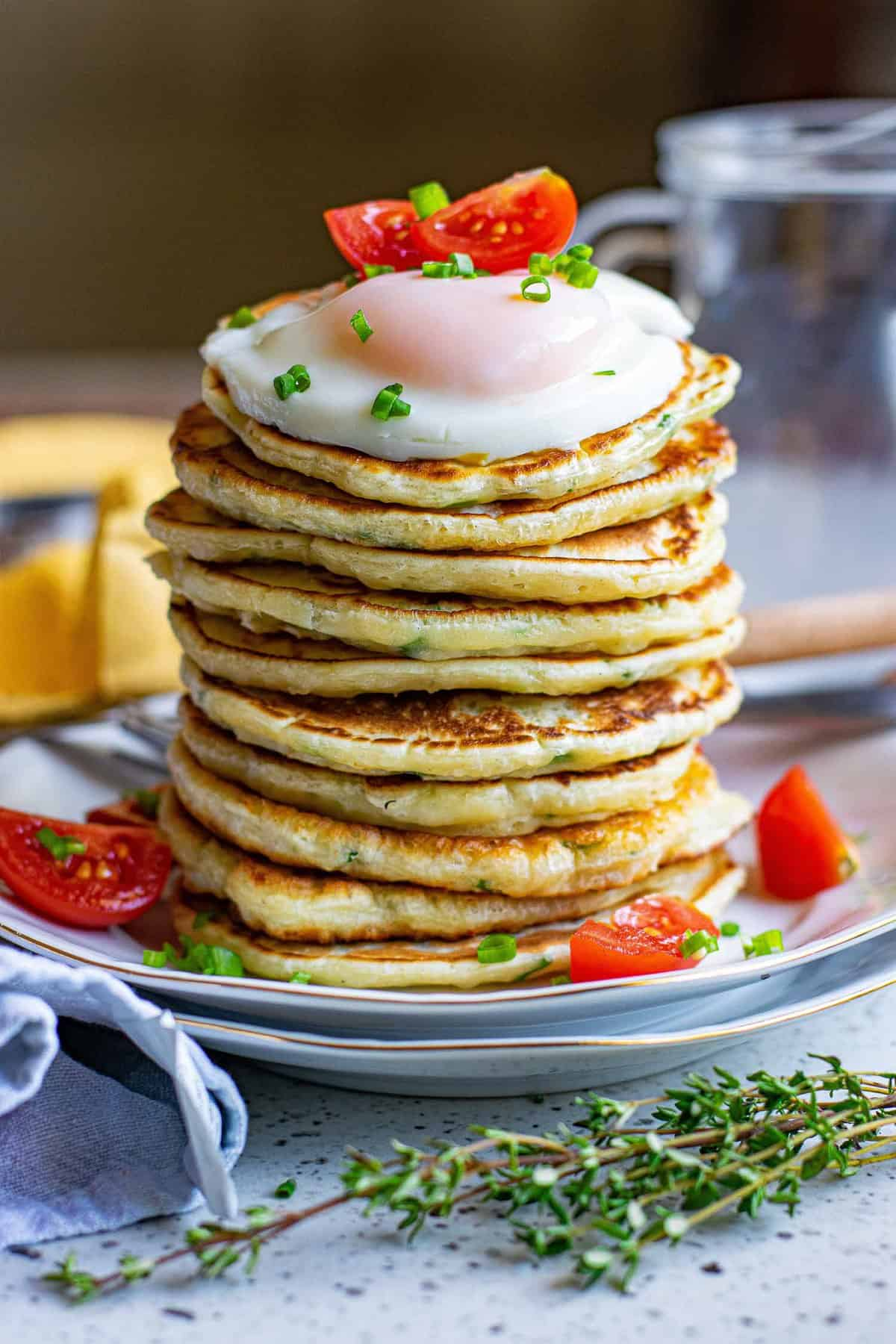 Tall stack of pancakes topped with a fried egg and cherry tomatoes.
