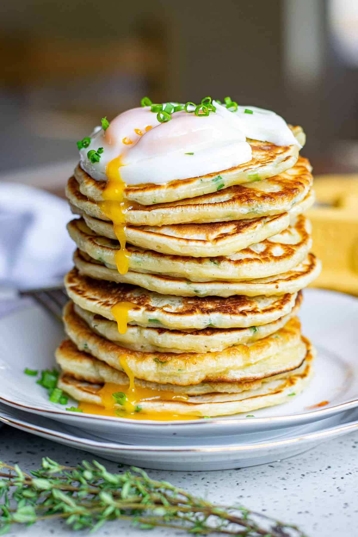 Tall stack of pancakes with a runny egg and chives on top.