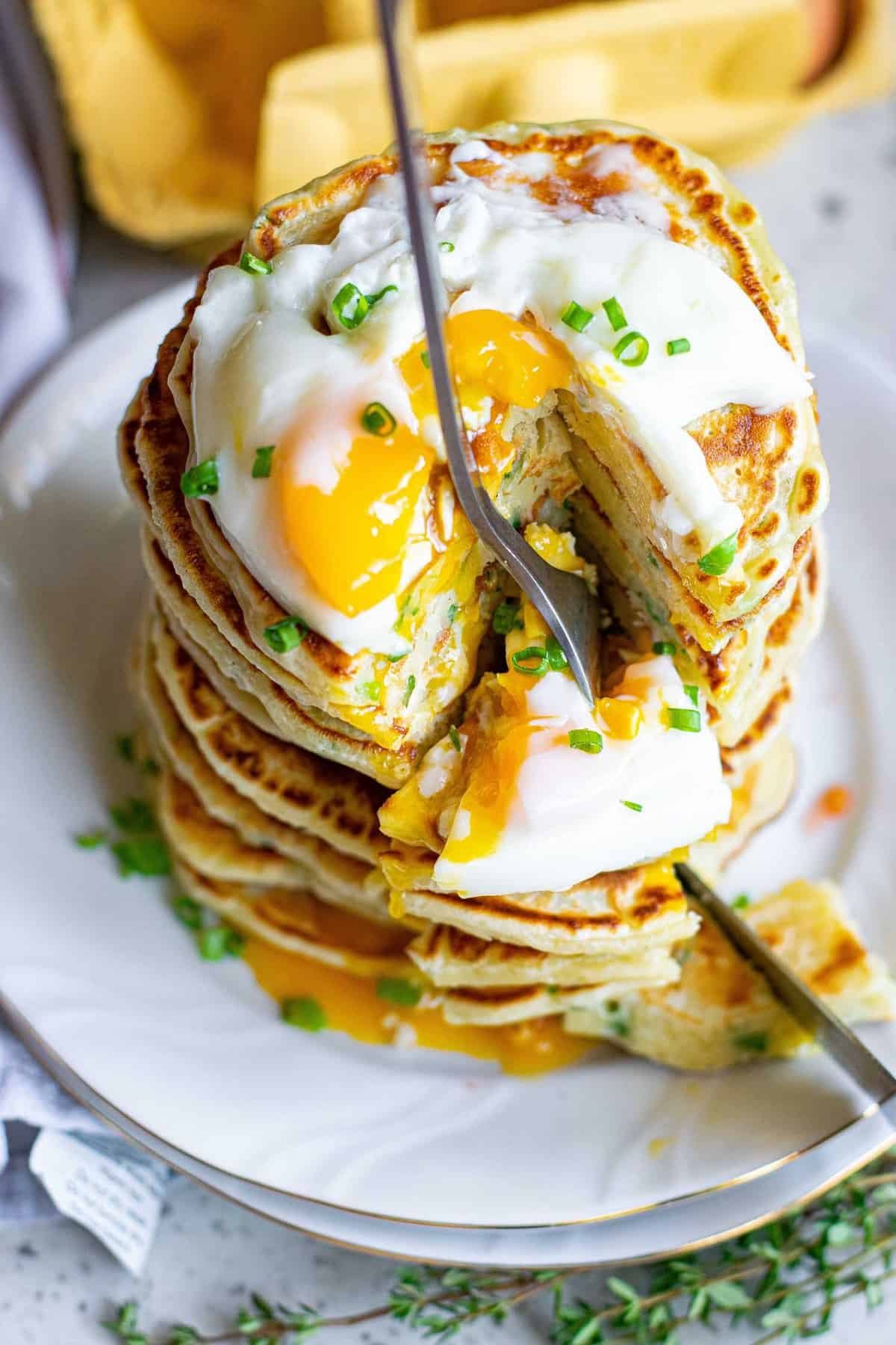 Overhead view of a fork stabbing into a stack of pancakes.