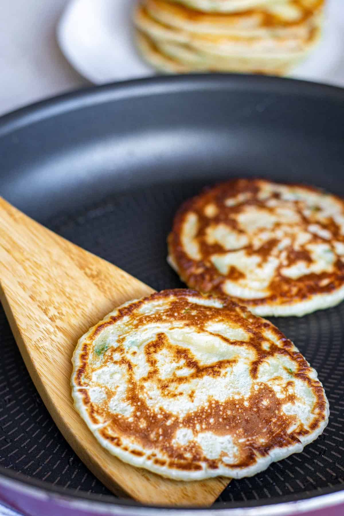 Pancakes being cooked in a frying pan.