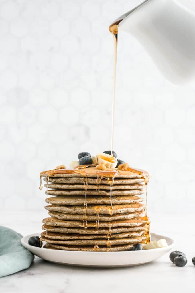 Syrup being poured on a tall stack of buckwheat pancakes.