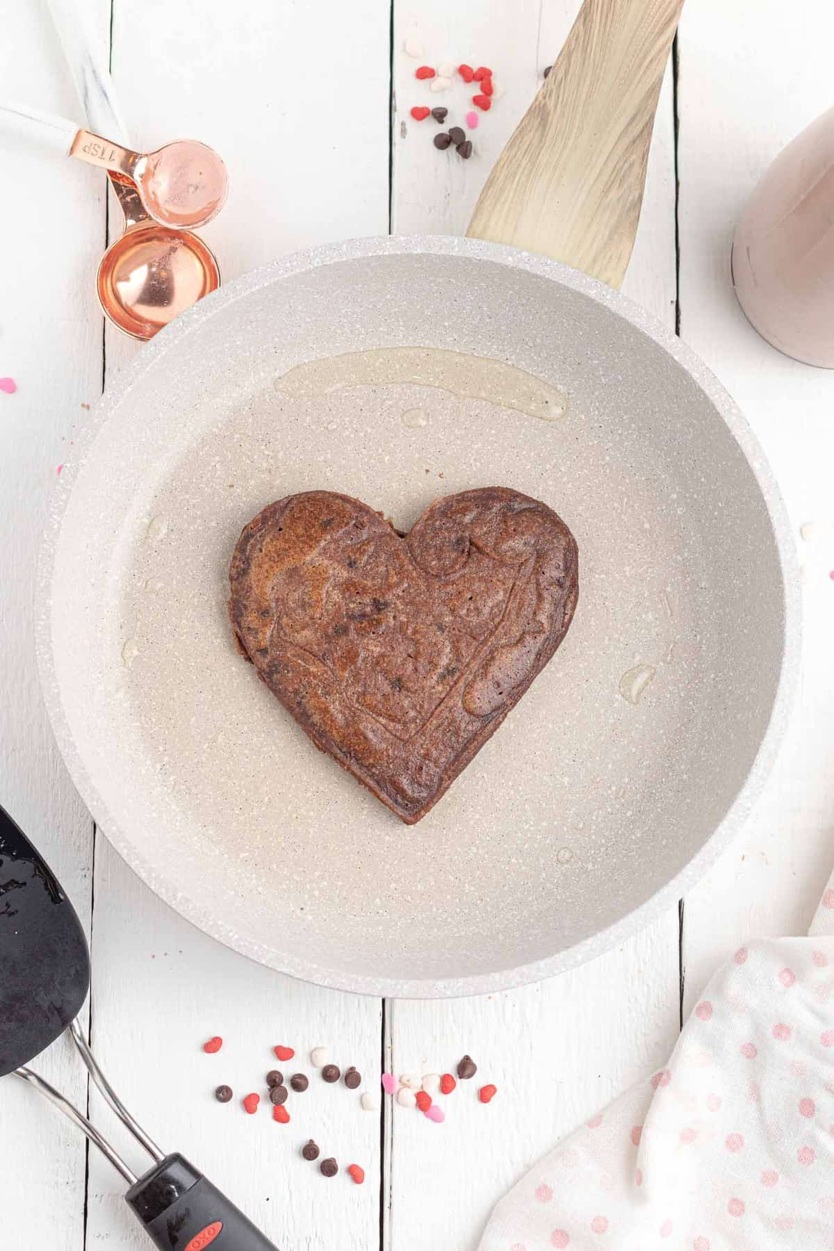 Heart shaped chocolate pancake on a white griddle.
