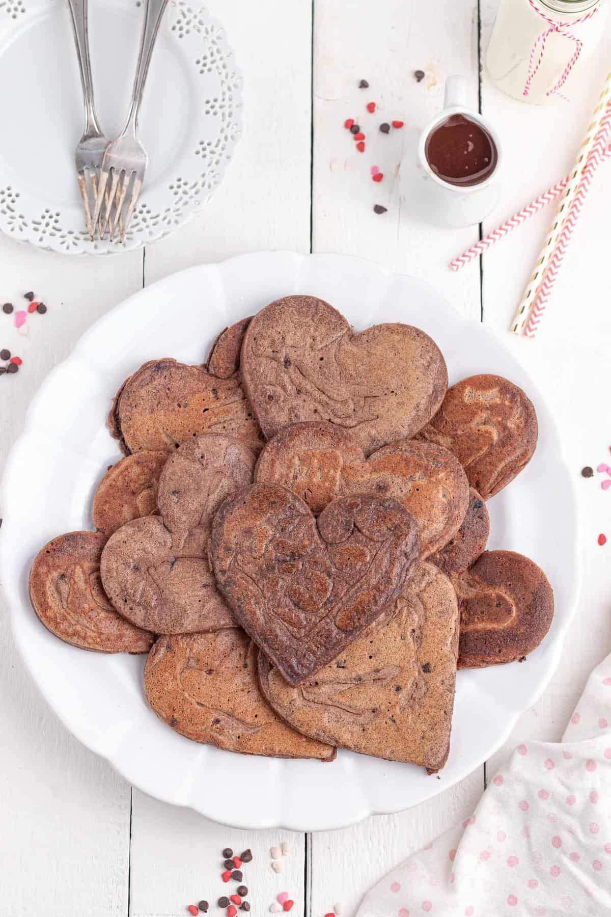 Messy pile of chocolate pancakes on a plate. Pancakes are heart-shaped.