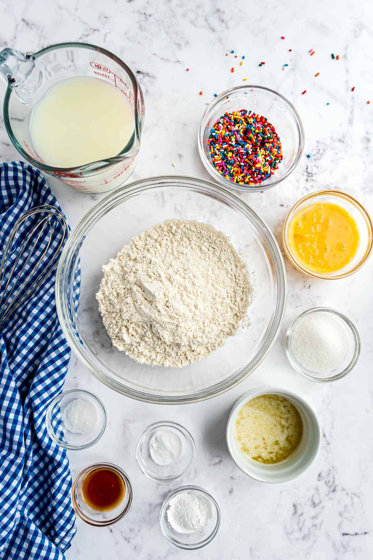 Clear glass bowls of ingredients: flour, eggs, vanilla, milk, sprinkles, and more.