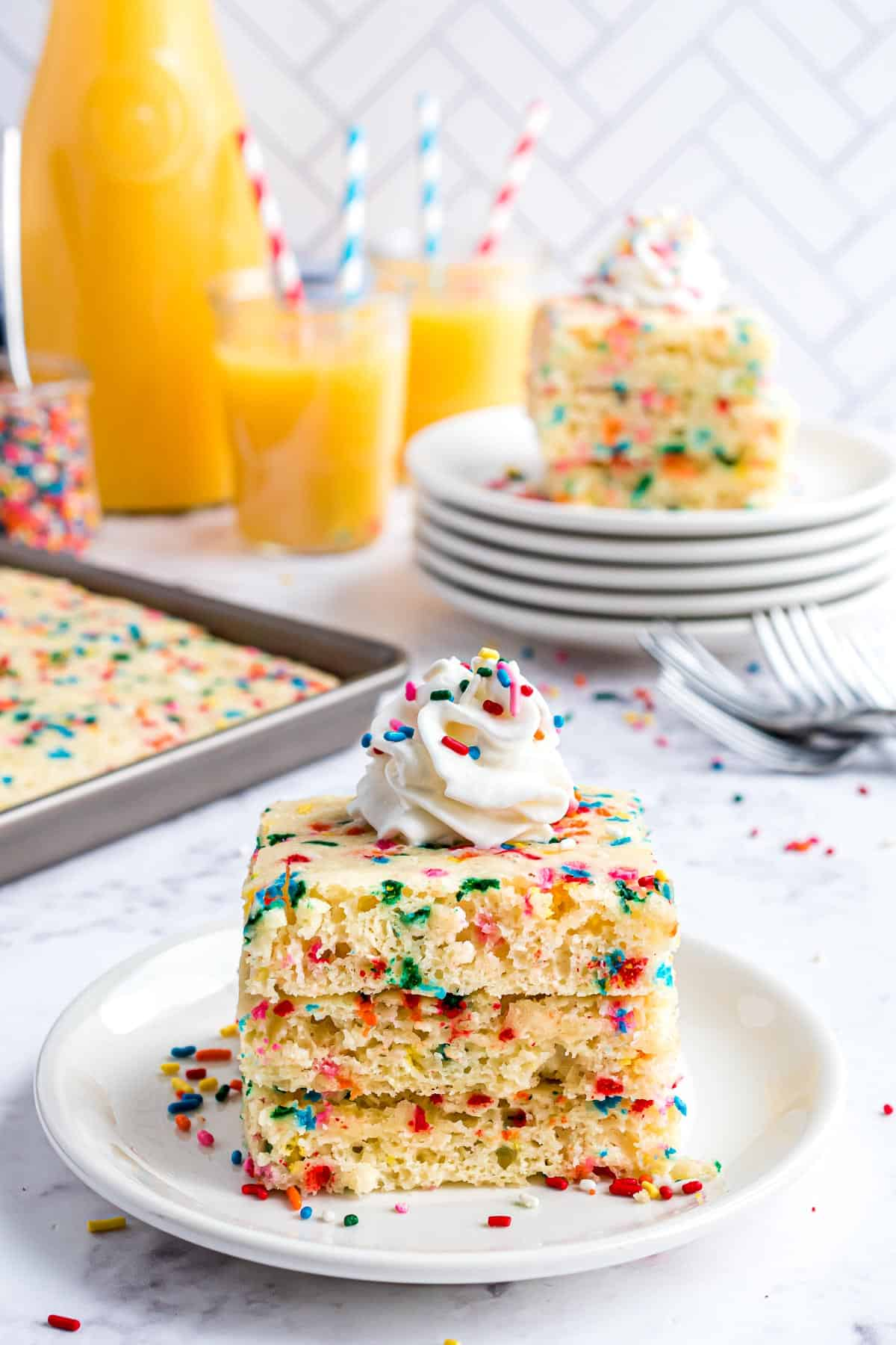 Three square pancakes with whipped cream and sprinkles.