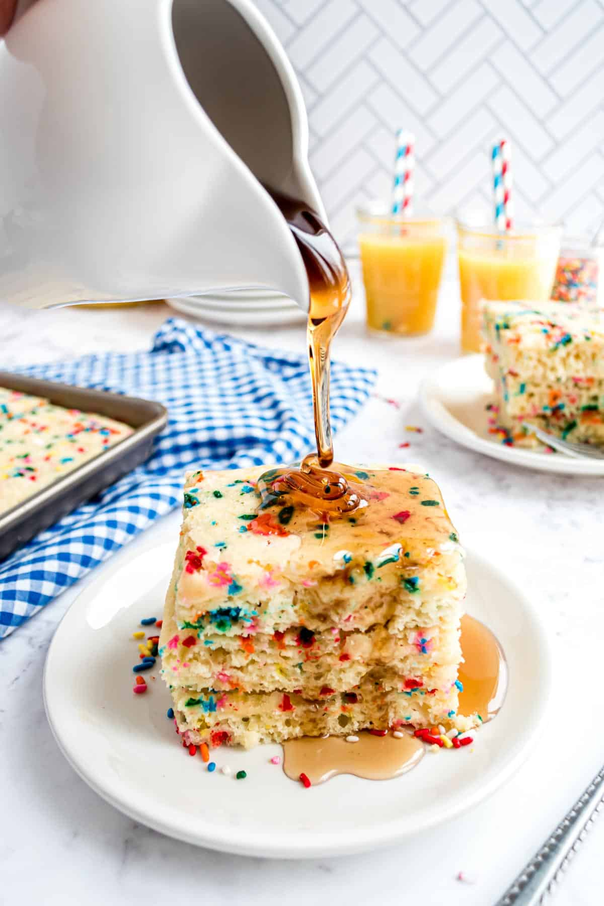 Syrup being poured on a stack of sprinkled pancaked.