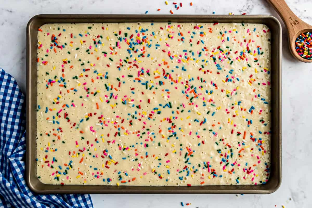 Unbaked sheet pan pancakes with sprinkles on top.