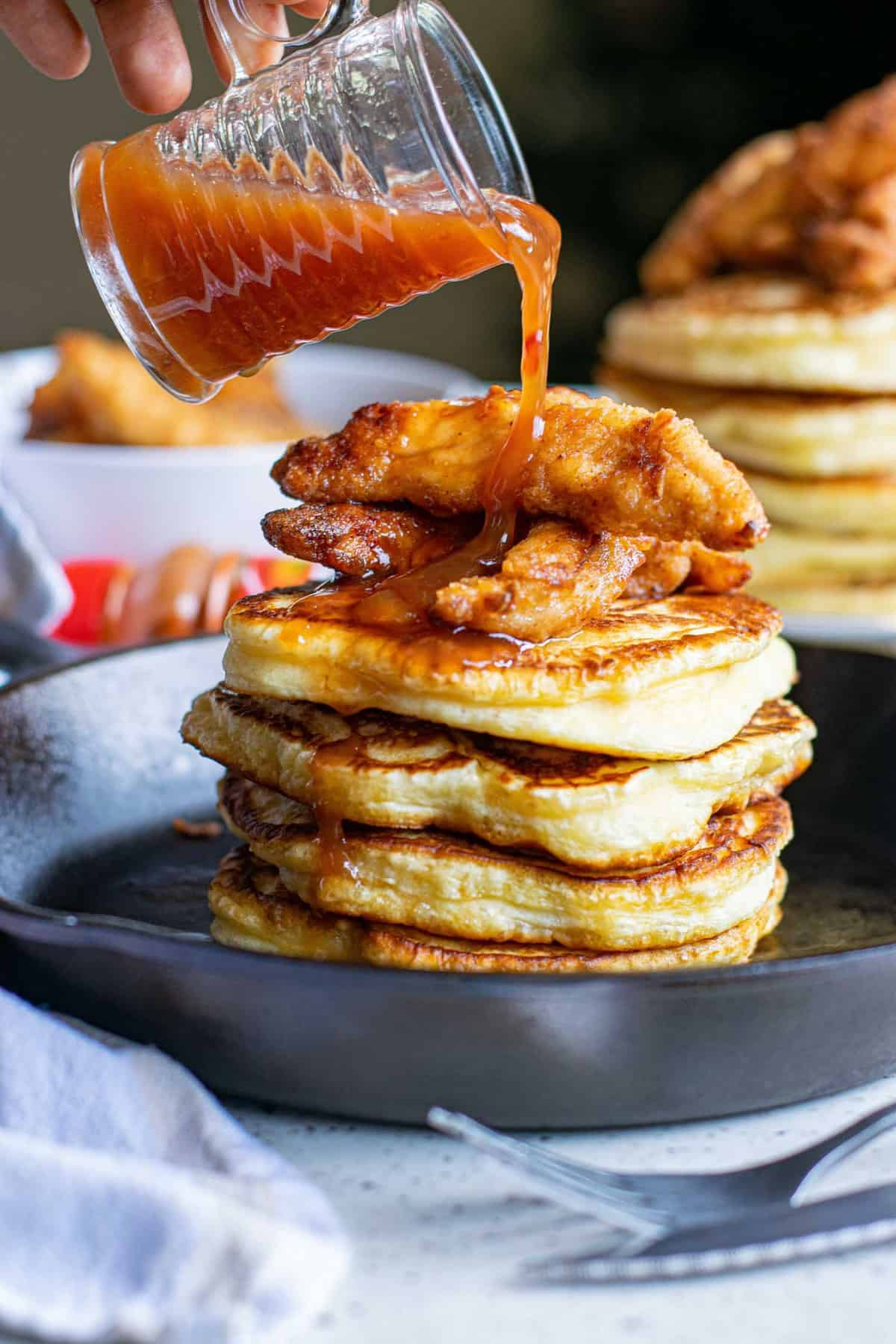 Red sauce being poured over a stack of pancakes and crispy chicken.