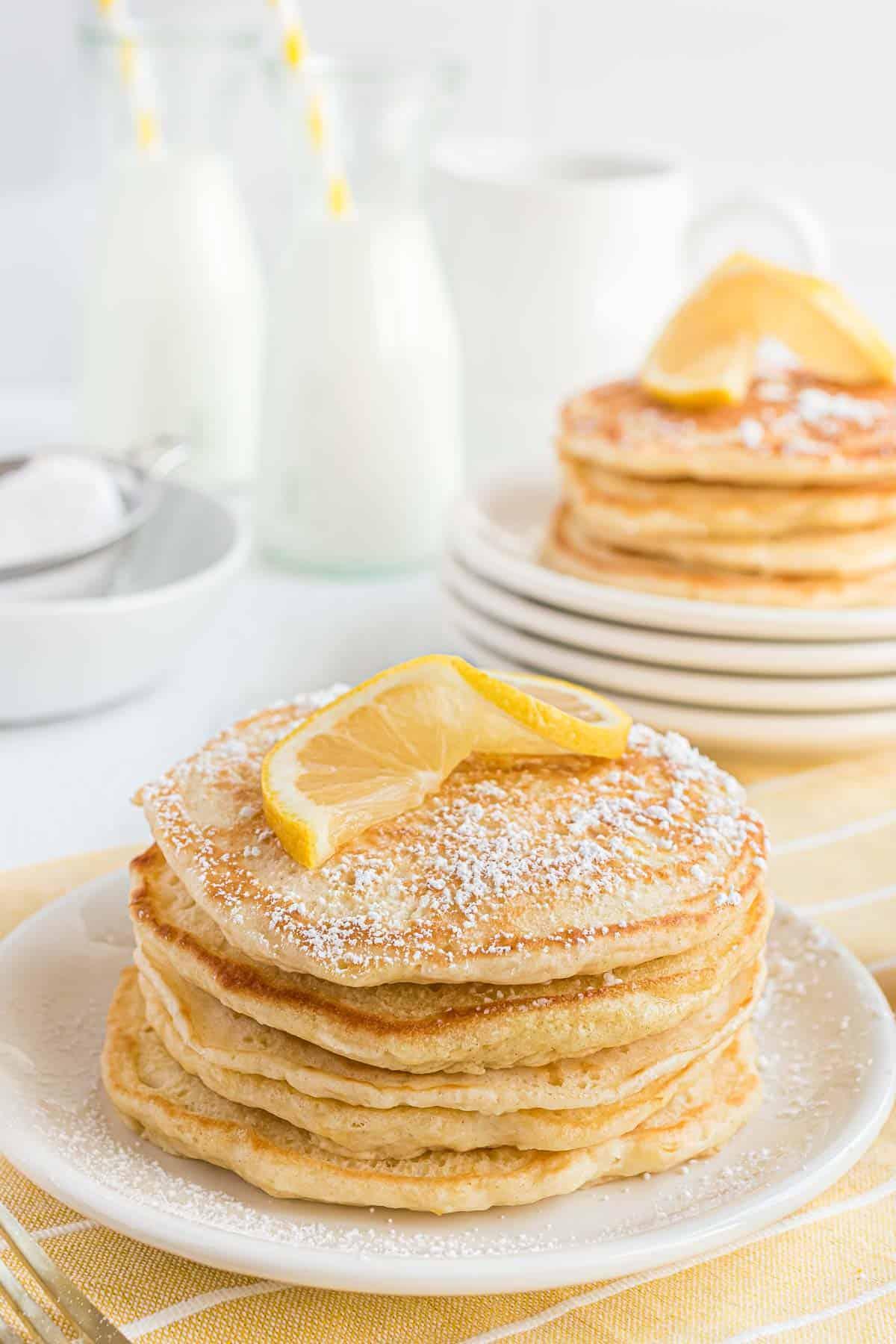 Stack of lemon pancakes topped with powdered sugar and lemon wheel.