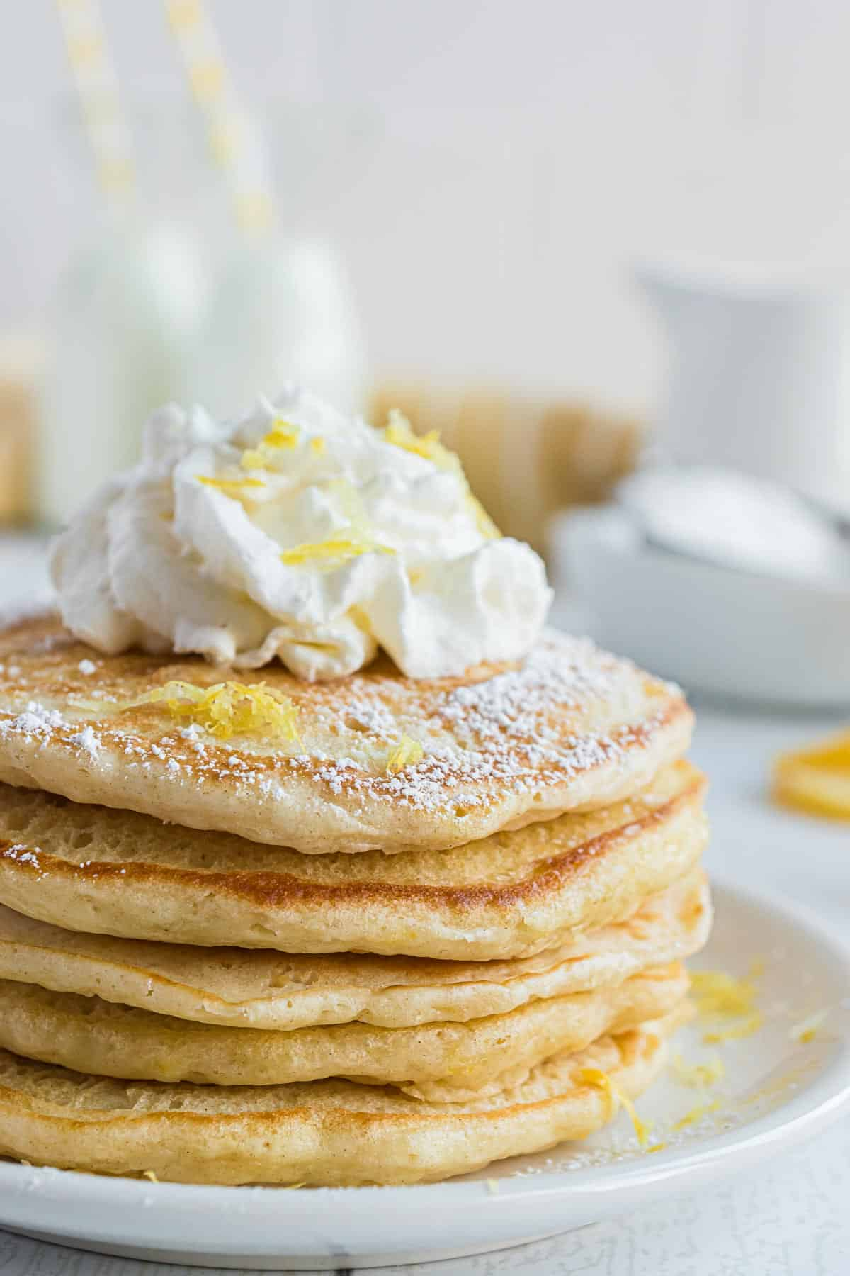 Stack of pancakes topped with whipped cream and lemon zest.