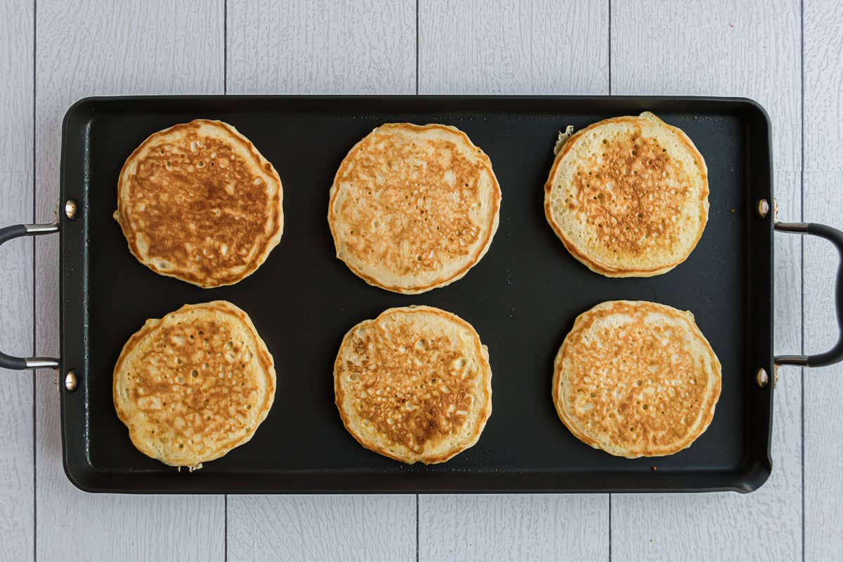 Cooked pancakes on black griddle.