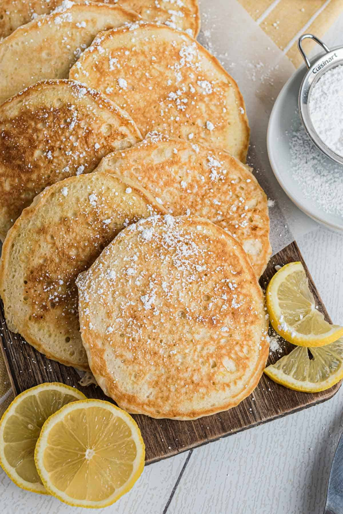 Pancakes on a platter with lemon slices.