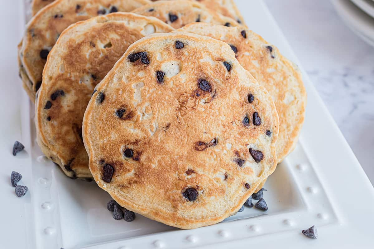 Peanut butter pancakes with chocolate chips, on a white platter.