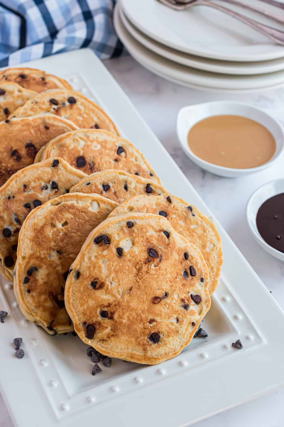 Pancakes studded with chocolate chips on a white platter.