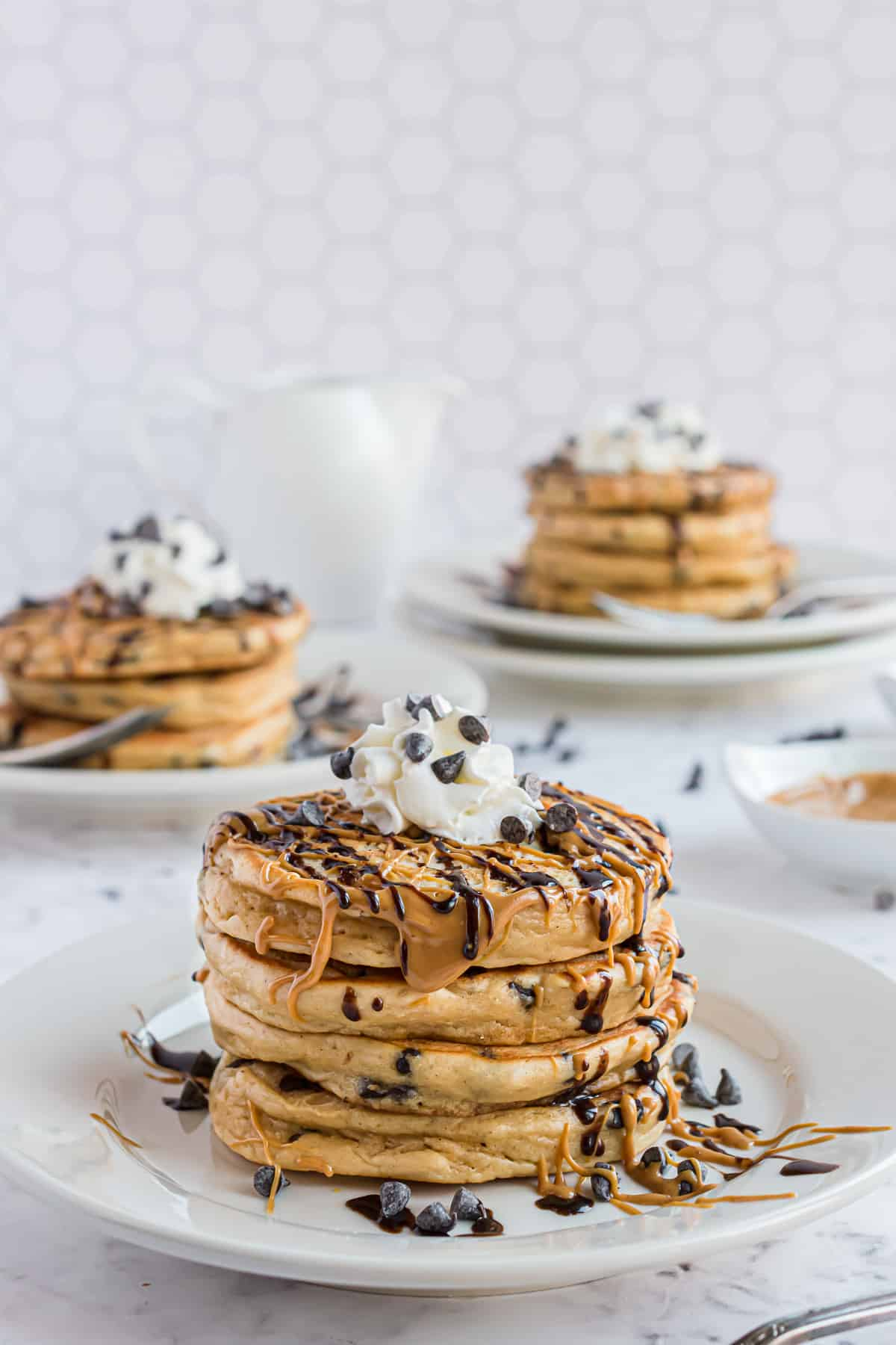 Three plates of stacked peanut butter pancakes.