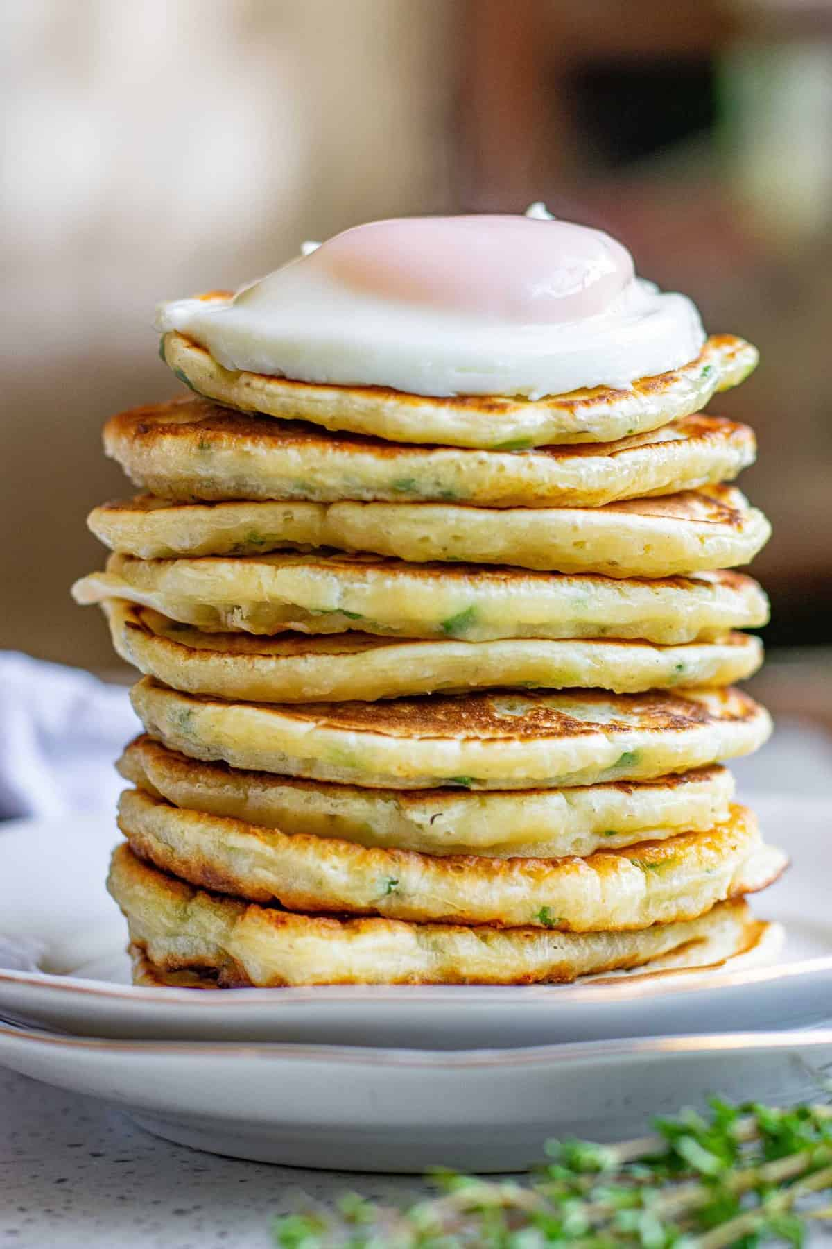 Very tall stack of pancakes topped with a perfect fried egg.
