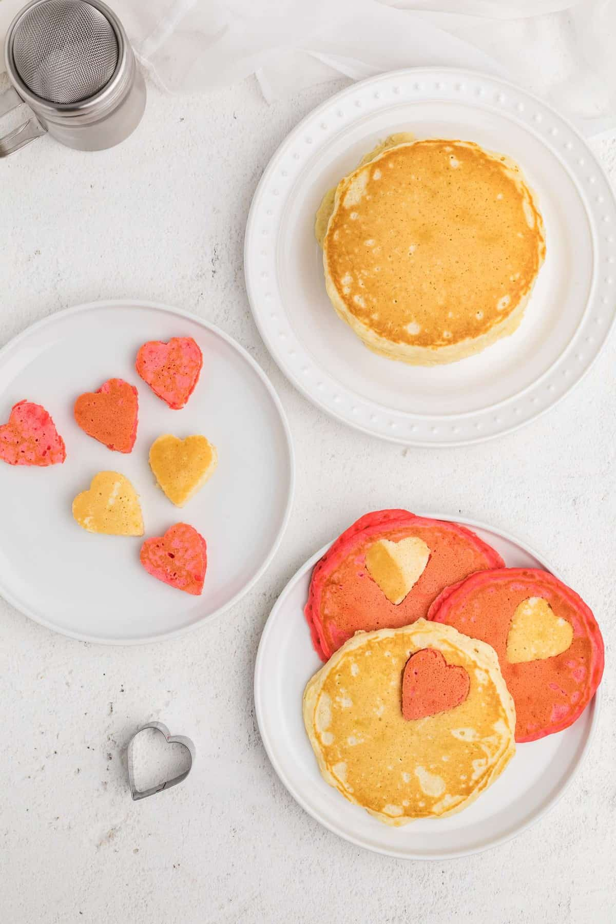 Overhead view of pink and white pancakes with heart shaped cut-outs.