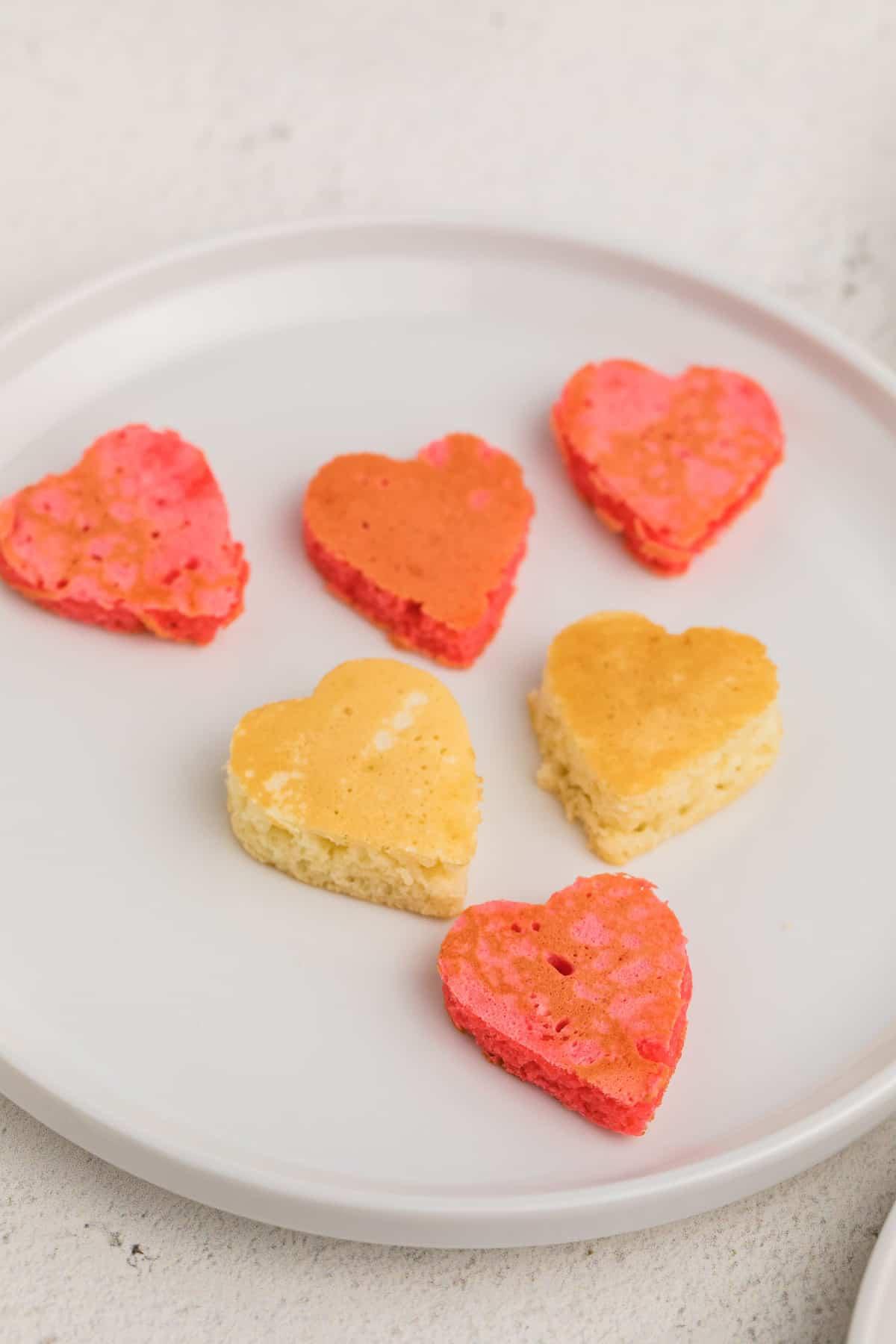 Tiny heart-shaped pancakes on a plate.