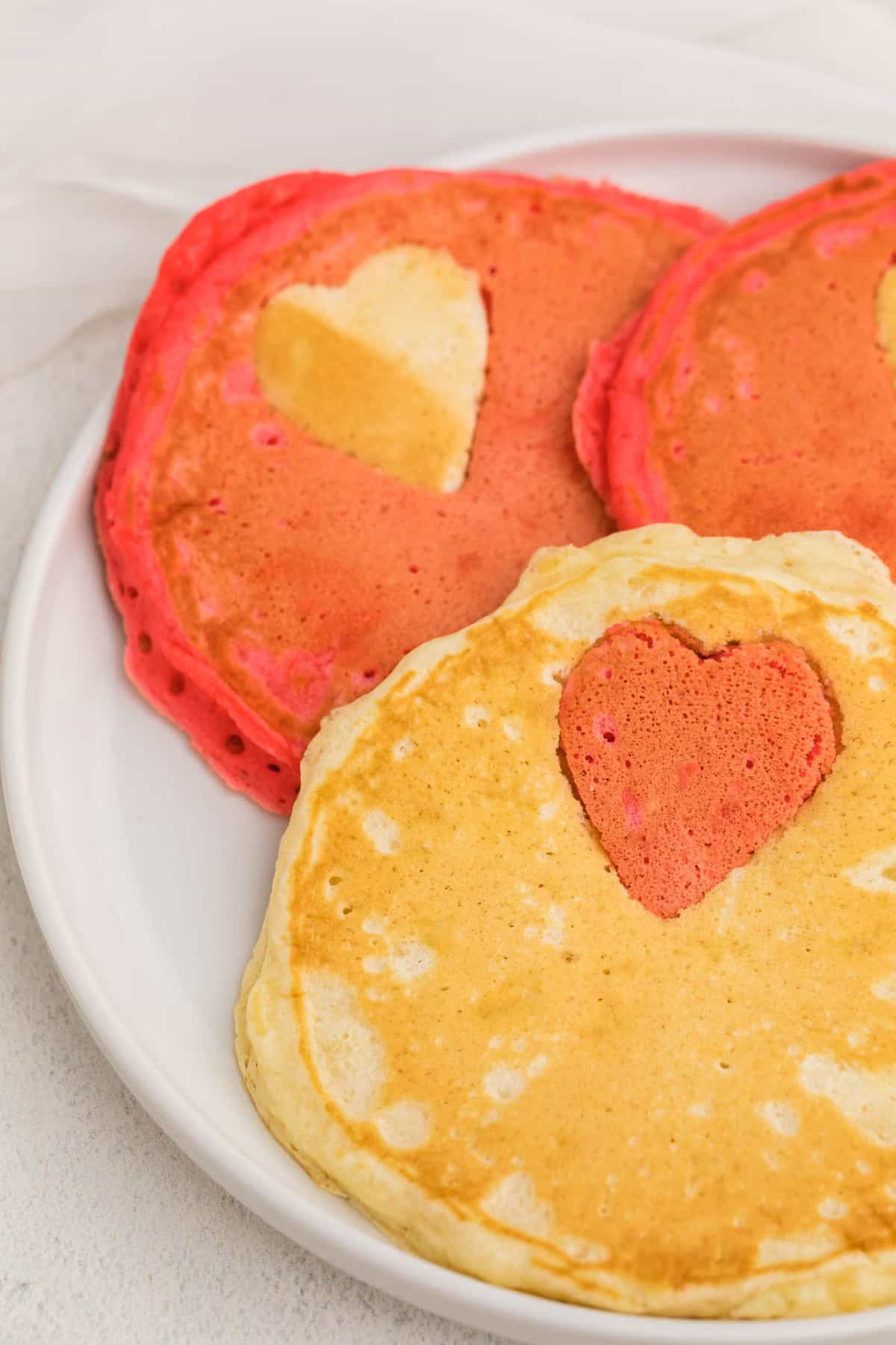 Close up of pancakes with contrasting color heart shape.