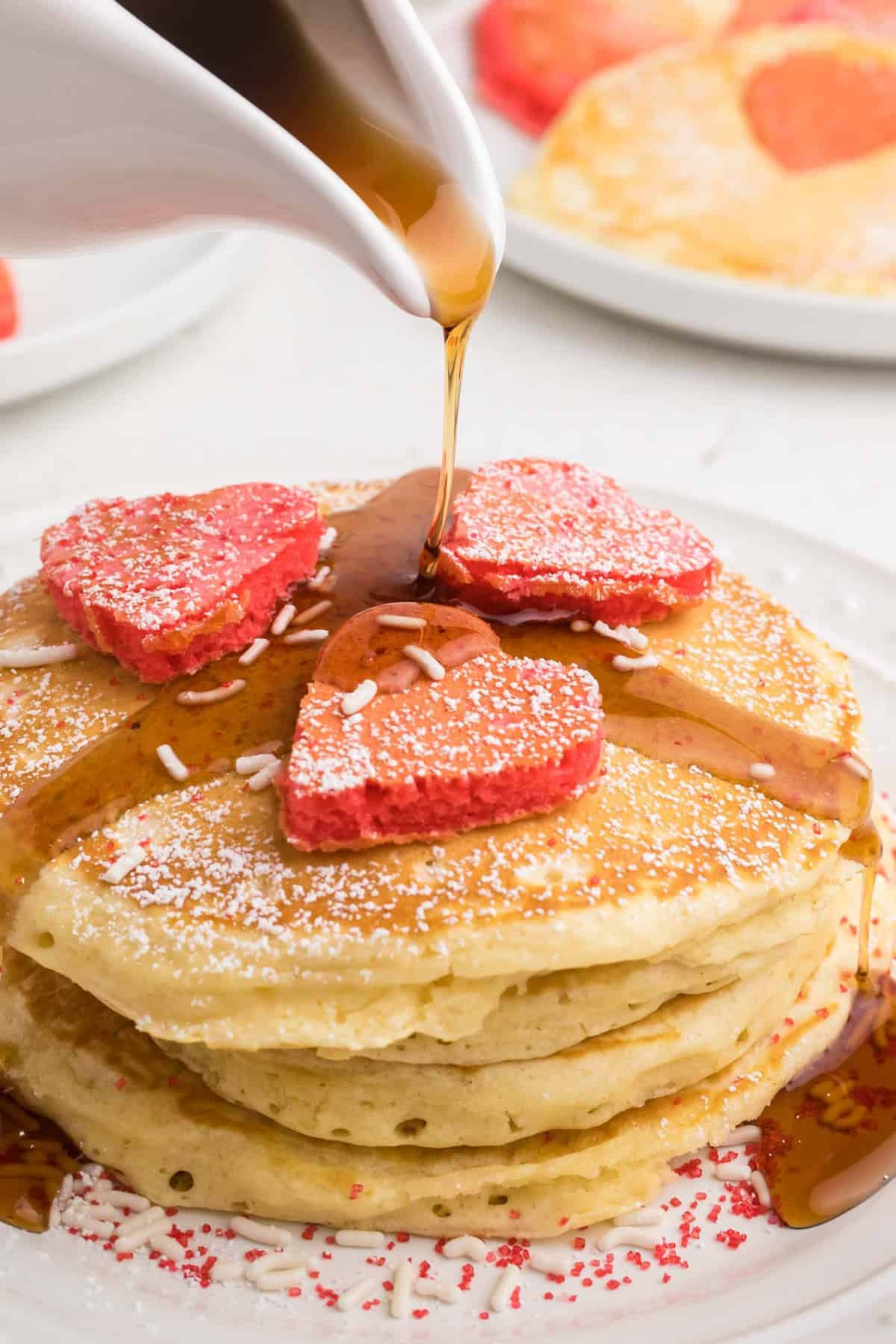 Syrup being poured onto pancakes with more heart-shaped pancakes on top.