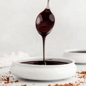 Chocolate syrup dripping off a spoon into a small bowl.