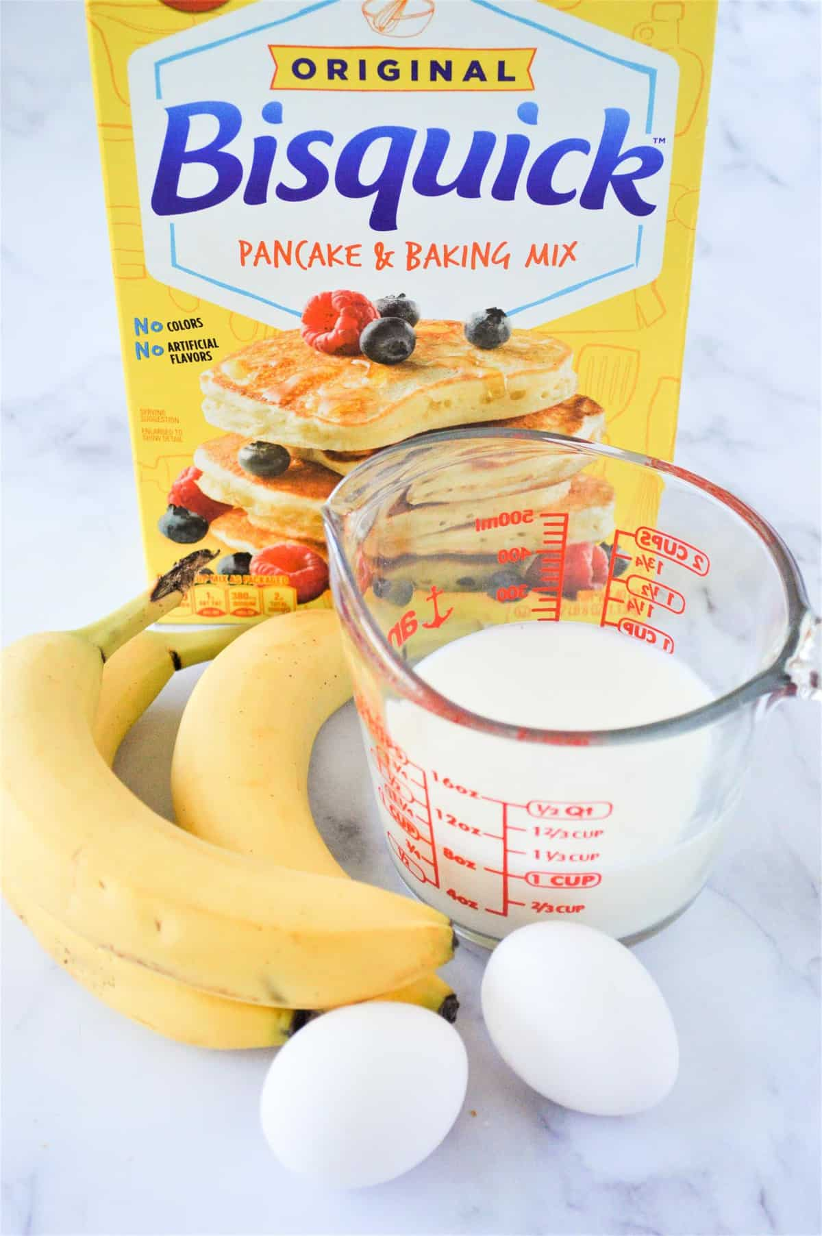 Three bananas, two eggs, milk in measuring cup, and a box of bisquick.