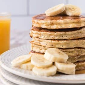 Stack of pancakes with sliced bananas.