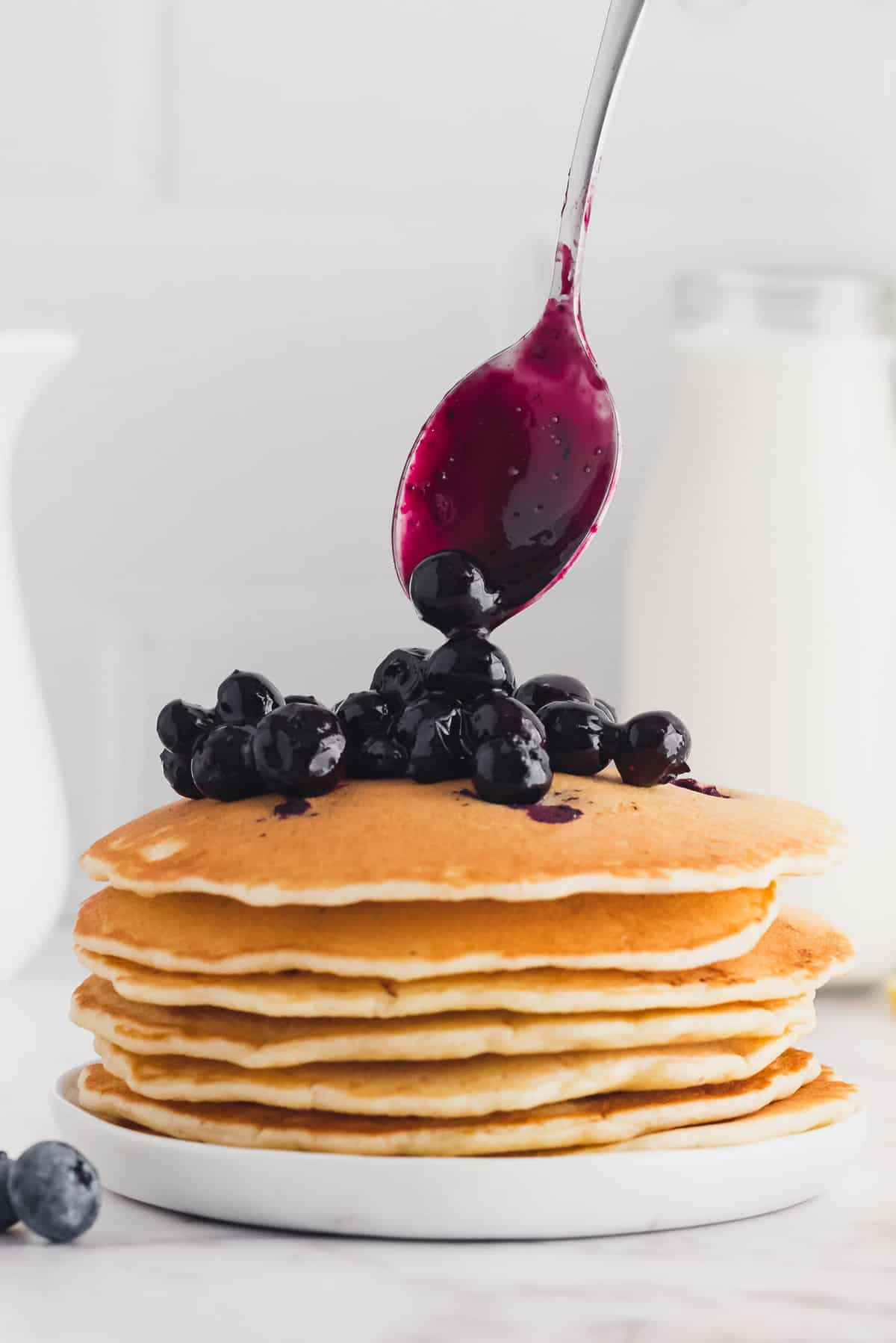 Blueberry sauce dripping down a stack of pancakes.