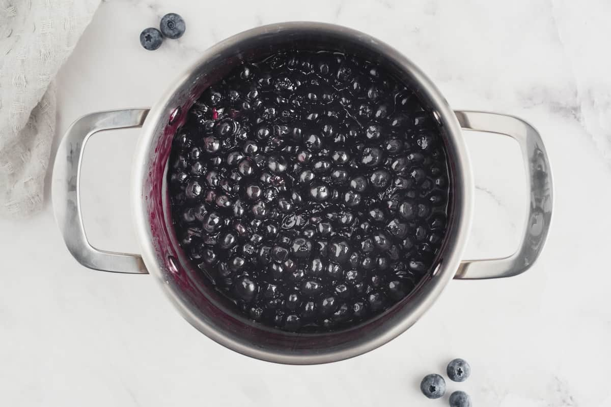 Cooked blueberry sauce in a metal saucepan.