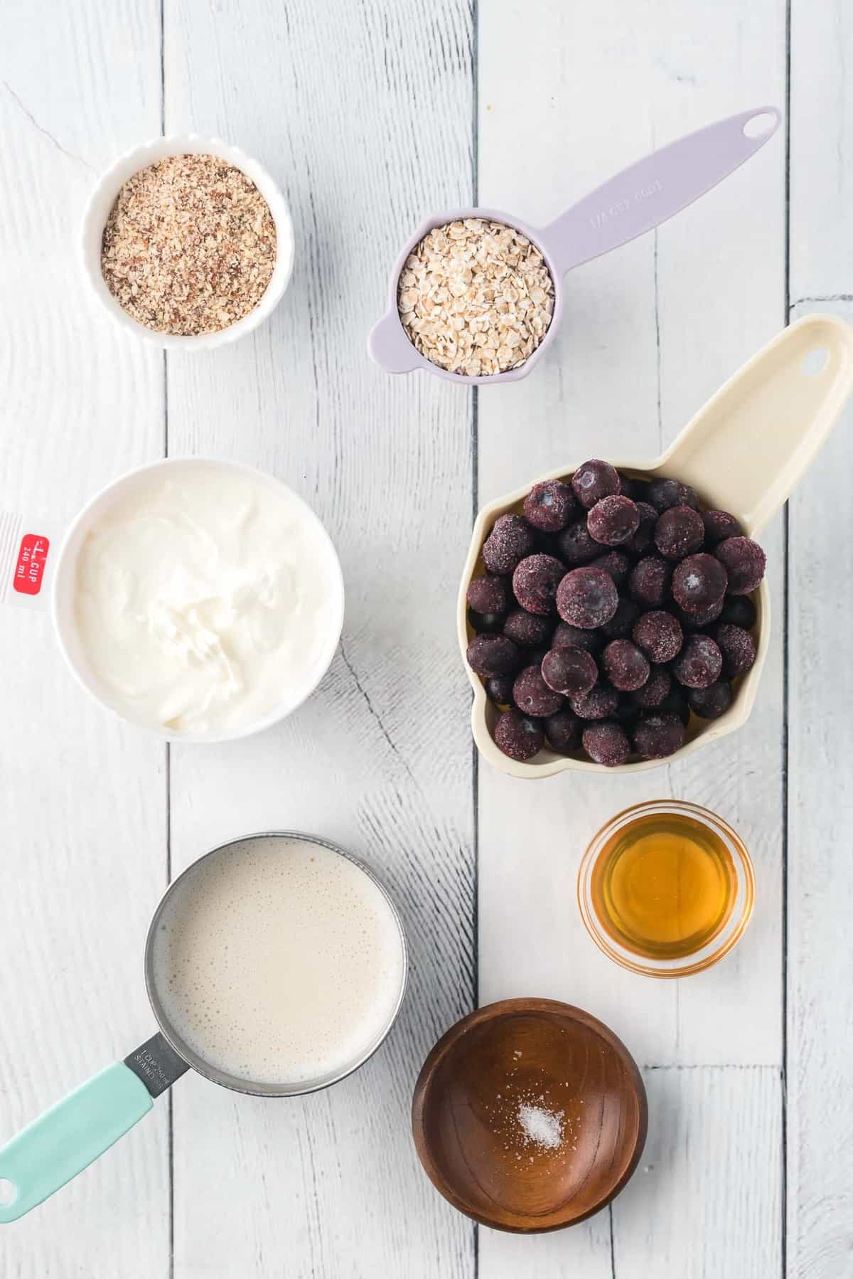 Small bowls of ingredients, blueberries, honey, almonds, yogurt, milk.