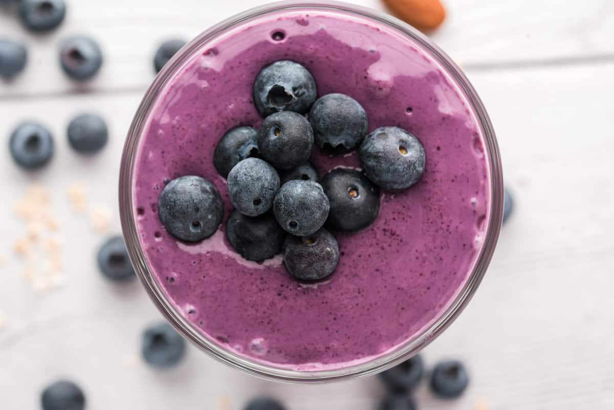 Pile of berries on top of a blueberry smoothie.