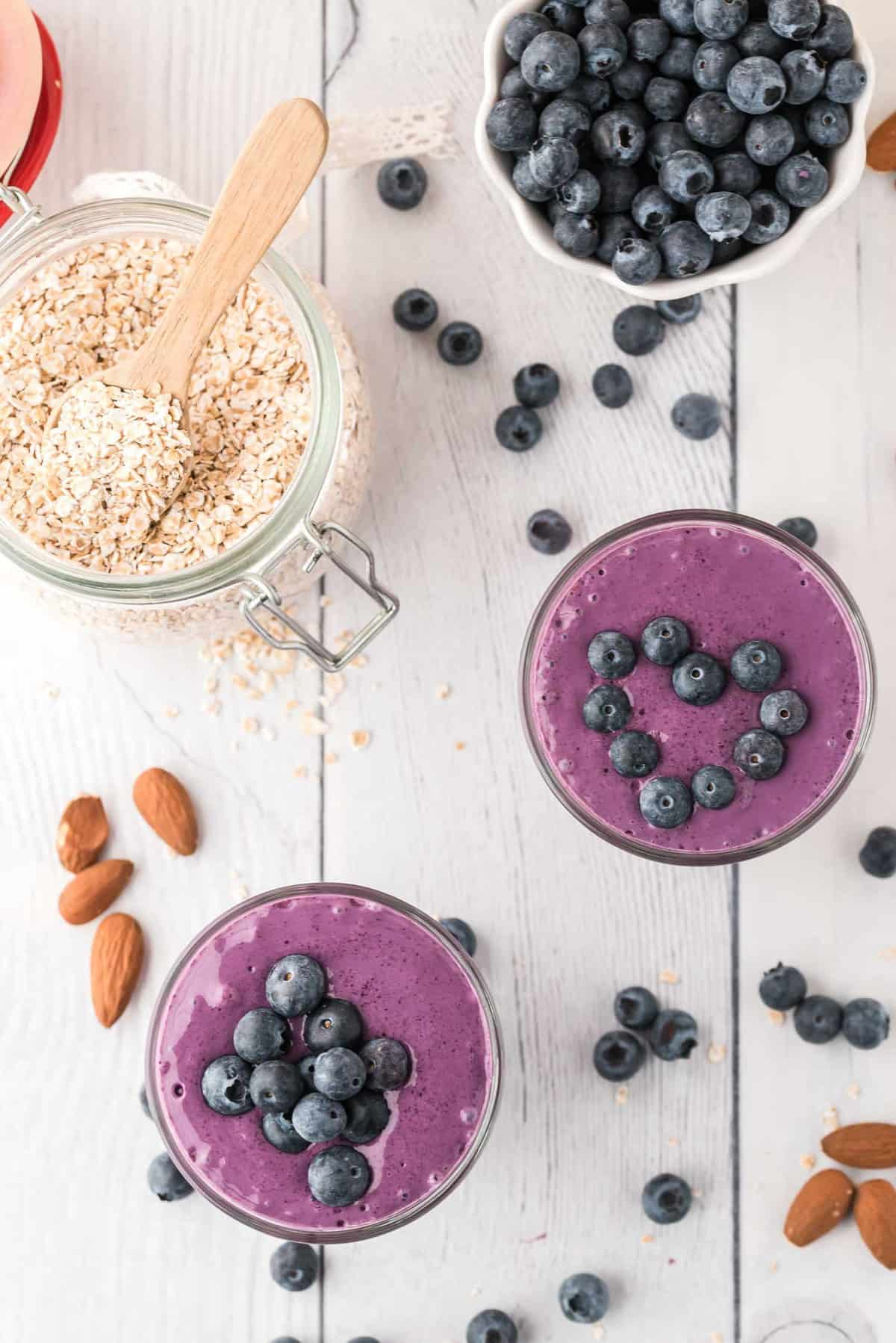 Overhead view of two blueberry topped smoothies, surrounded by a variety of ingredients.
