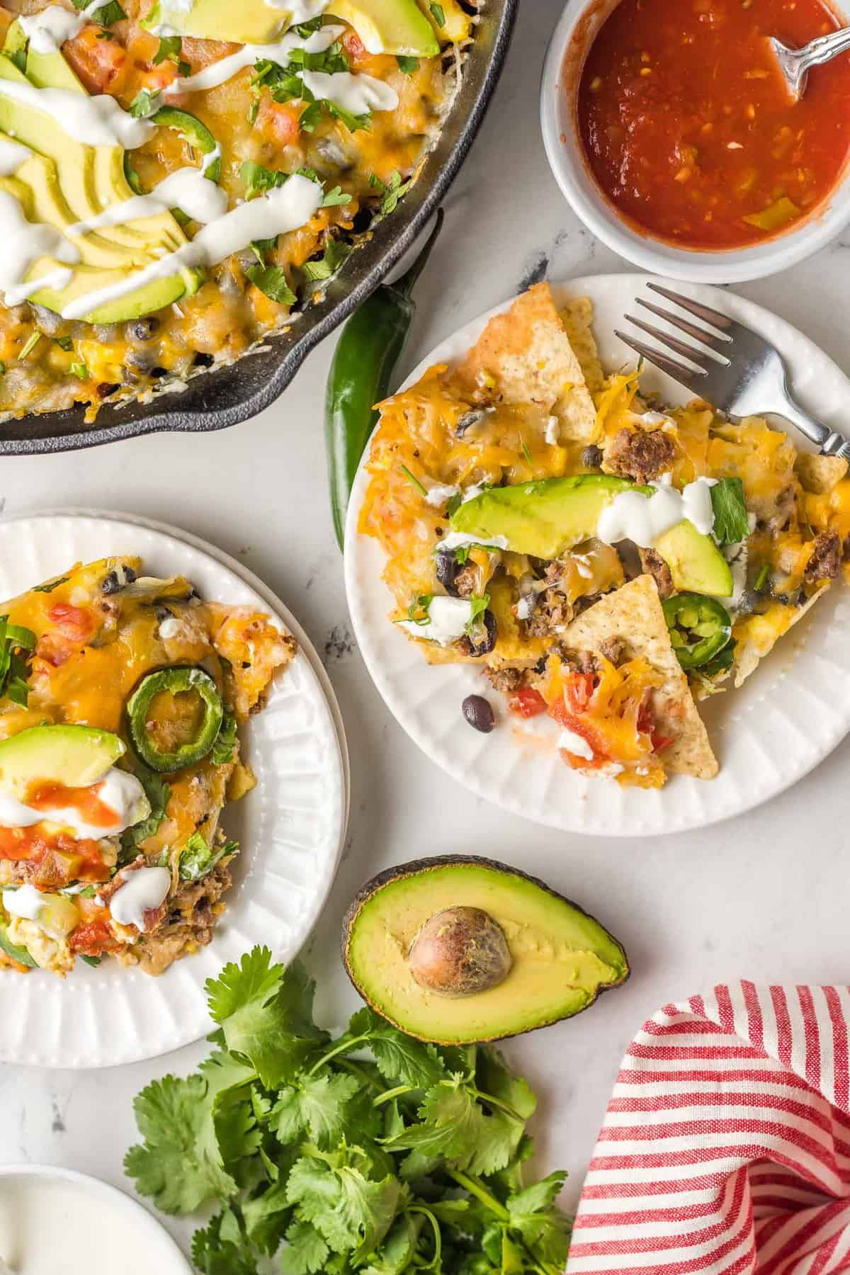 Overhead view of two plates and one skillet full of breakfast nachos.