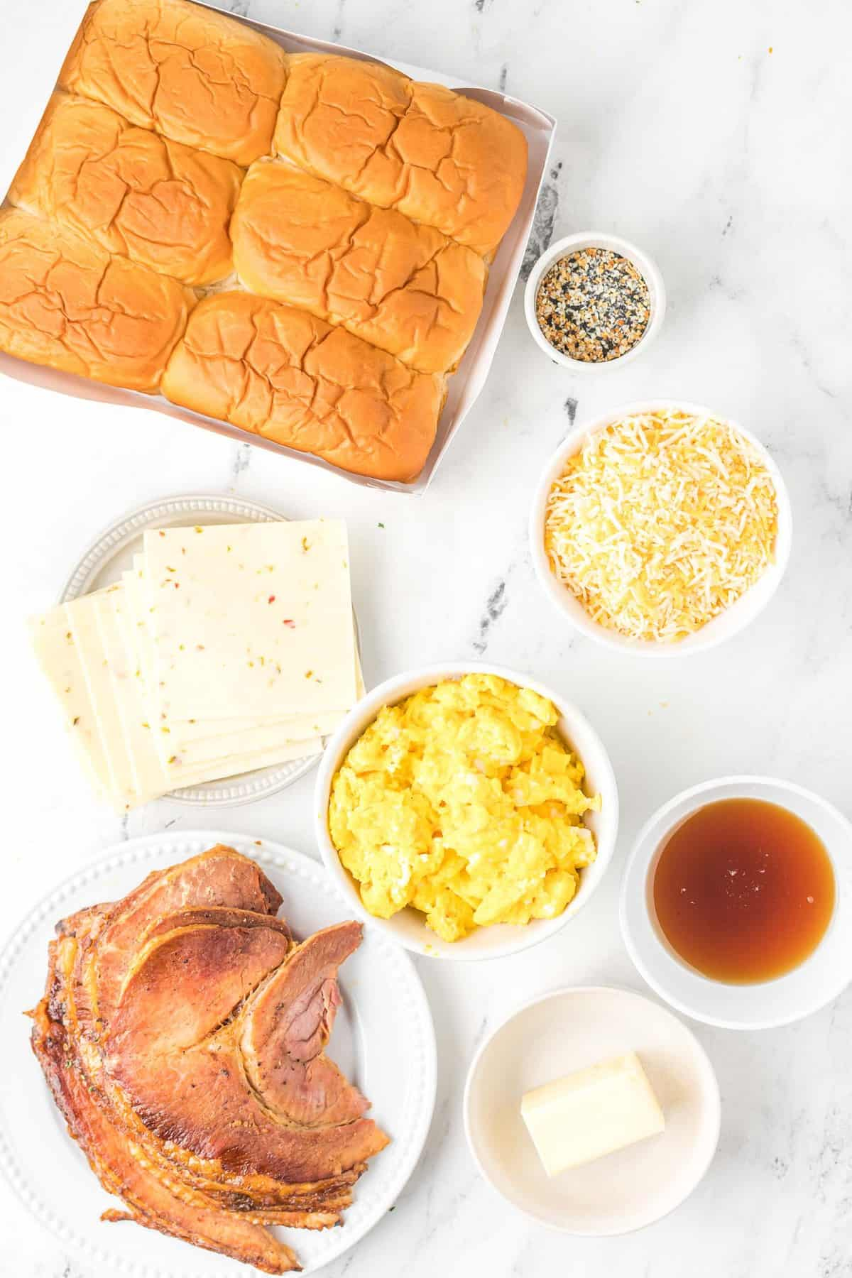 Overhead view of ingredients: rolls, ham, eggs, cheese, maple syrup, butter, and everything bagel seasoning.
